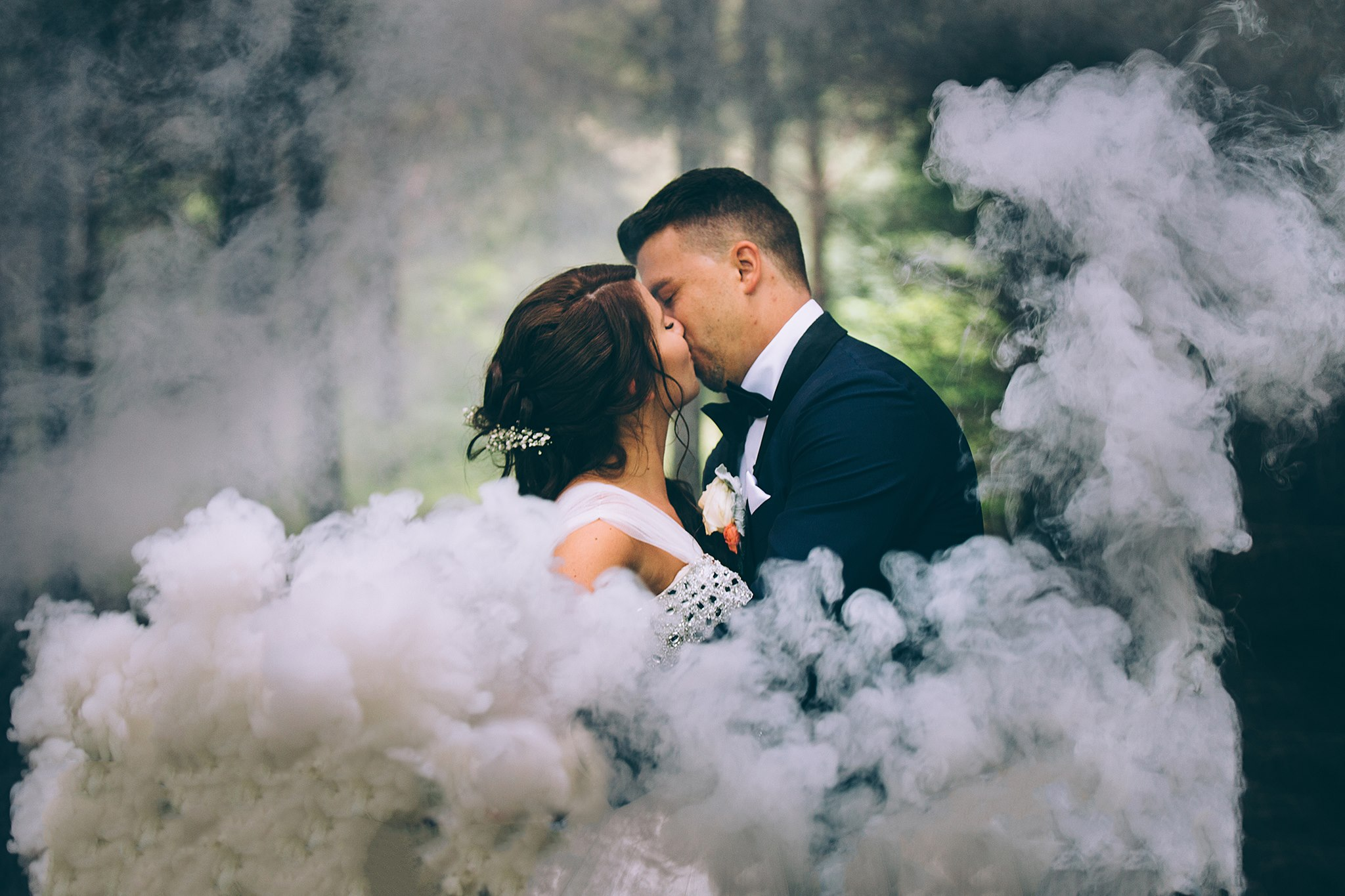 a bride and groom kissing with smoke billowing all around them