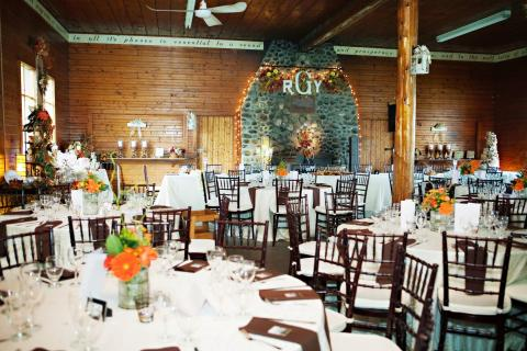 A rustic room set for a wedding with decorated tables.
