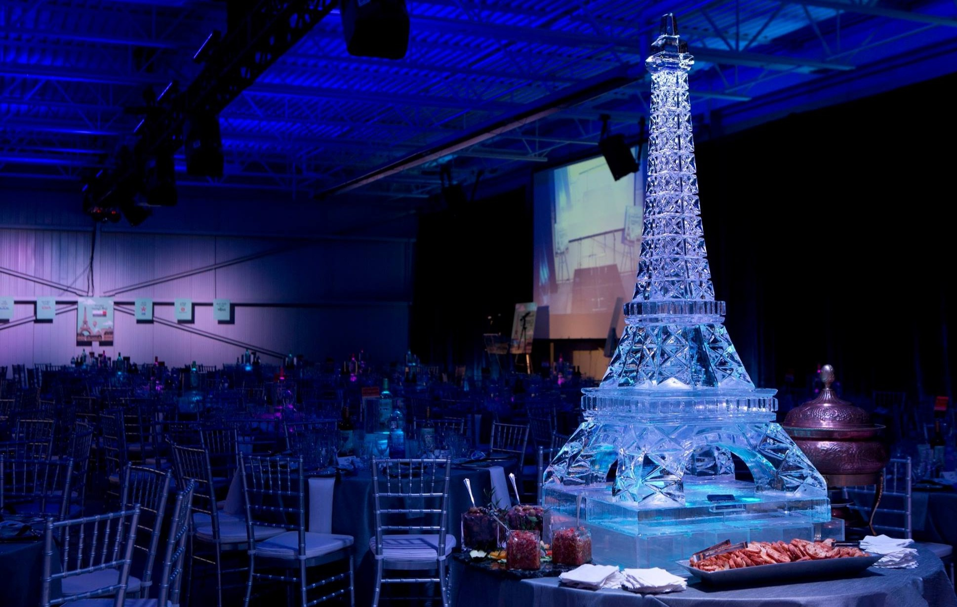 an ice sculpture in the shape of the Eiffel Tower on a table with hors d'oeuvres