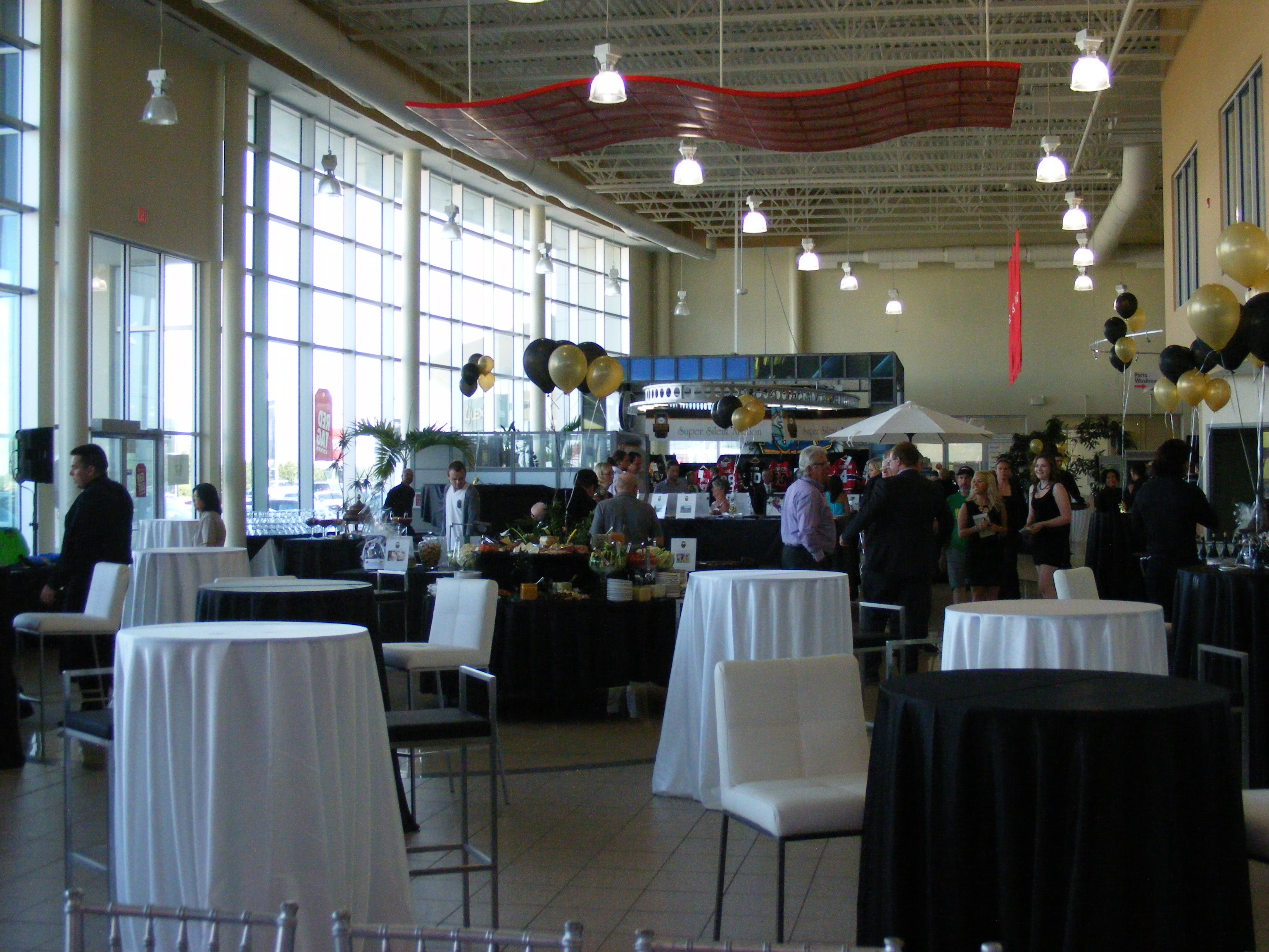 a dealership setup for an event with high bar top table scattered about