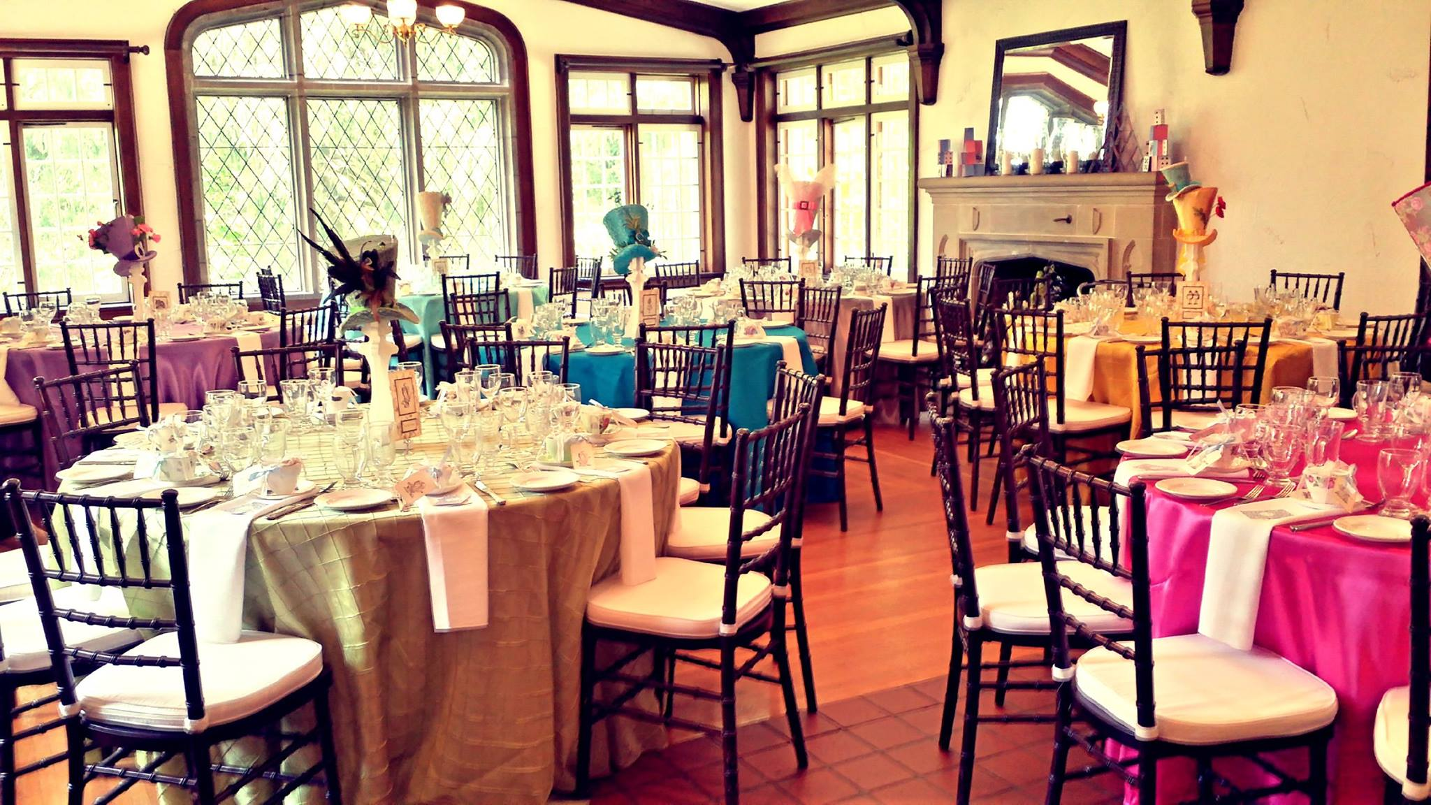 a room filled with tables and chairs set for dinner with different brightly coloured tables clothes and top hat centerpieces styled like Alice in Wonderland