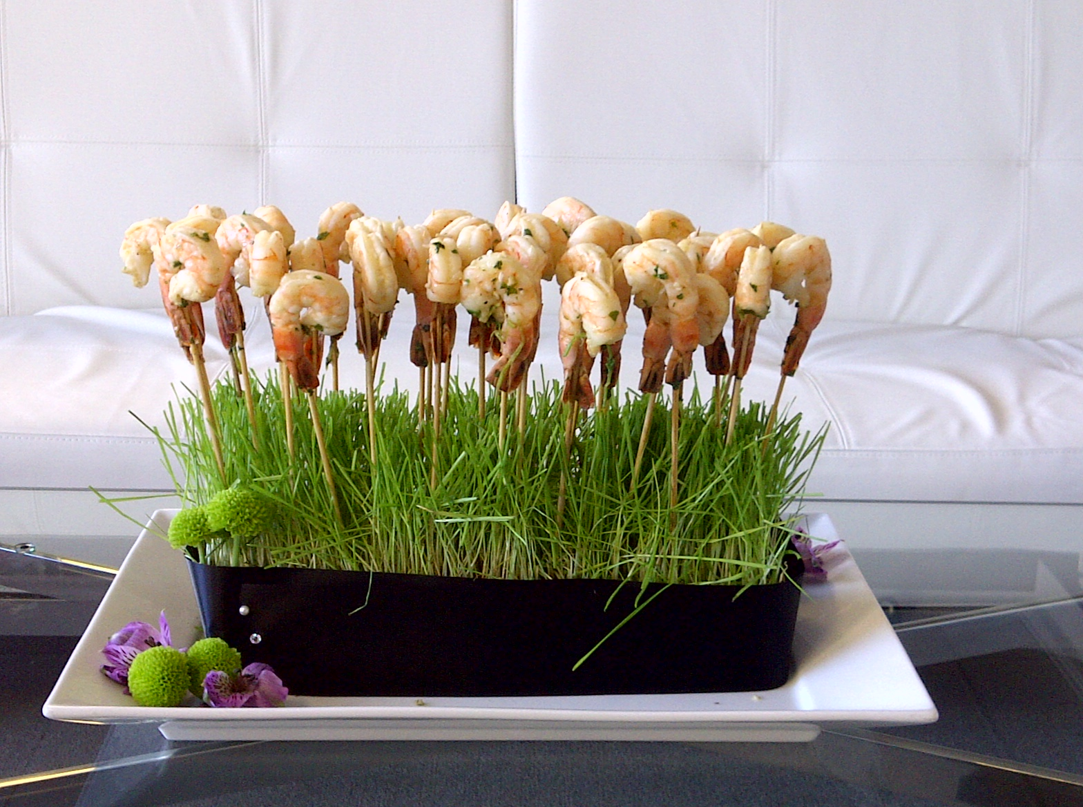 skewers of shrimp in grass on a glass coffee table in front of a white couch