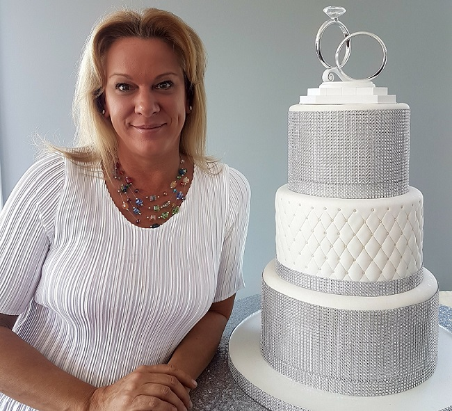 a lady standing beside a wedding cake