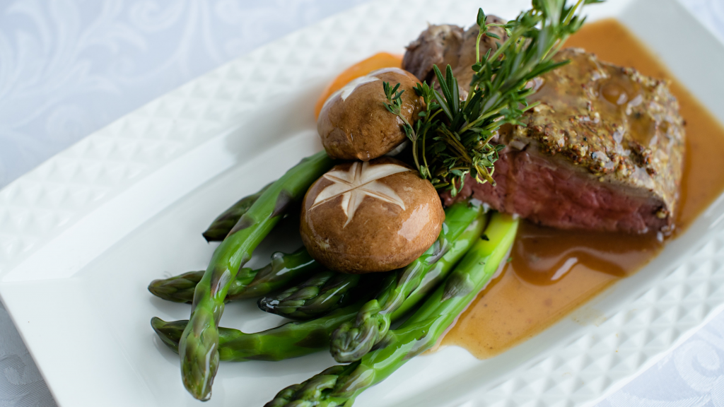 Rectangular plate with roast beef, asparagus, mushrooms and a carrot covered in gravy