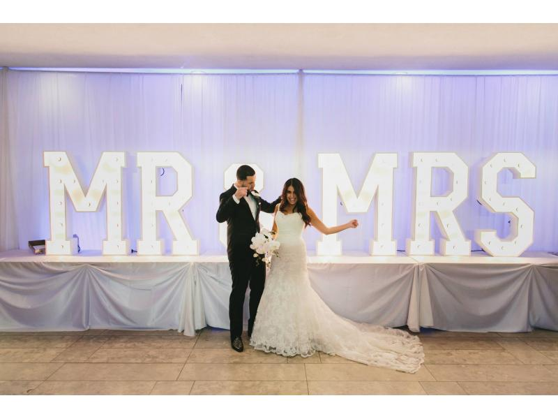 A bride and groom standing in front of a big sign that says Mr & Mrs