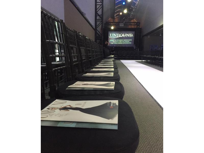 Close up of chairs with a magazine on the cushion, lining a runway with a sign in the back that says Unbound