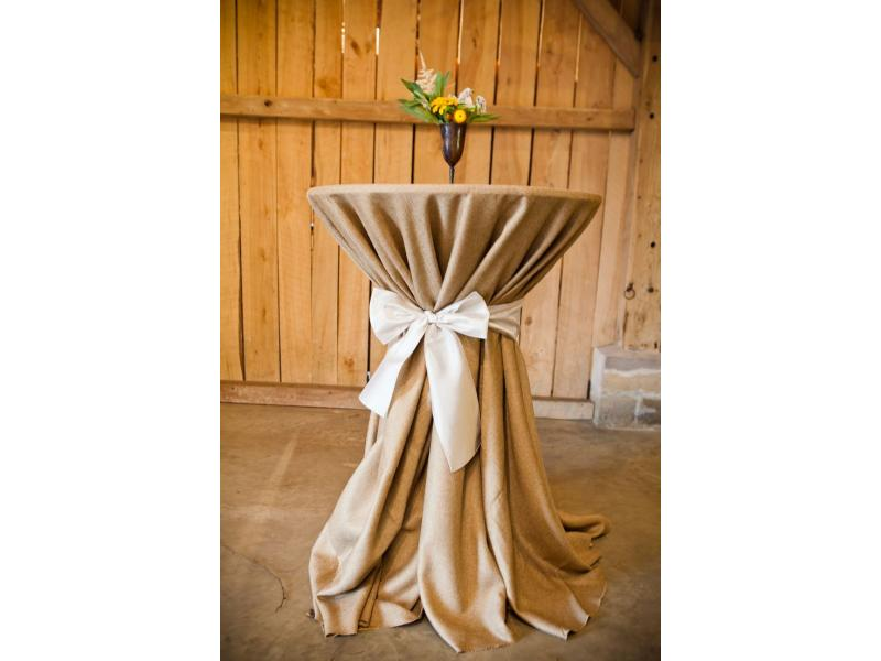 High bar top table with burlap table cloth and a bow tied around