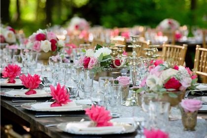 a long table with gold chairs, set for dinner with floral centerpieces
