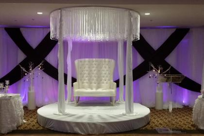 a loveseat on a stage with a chandelier tent above