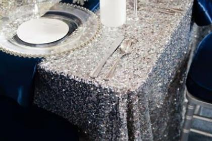 silver sequin table clothed table with clear charger plates and white floral centerpieces