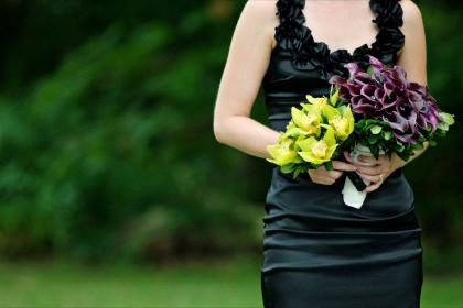 a lady in a black dress holding two bouquets
