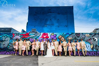 A wedding party wearing sunglasses standing in front of a wall full of graffiti