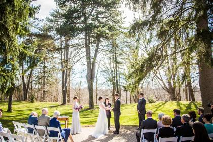 Ceremony on a patio with tall trees in the background