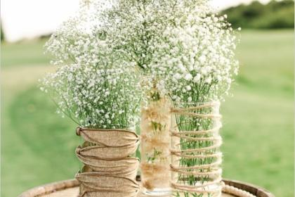 Wine barrel with vases on top filled with baby's breath